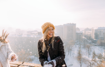 Blonde woman having a snowball fight with a yellow wooly hat on